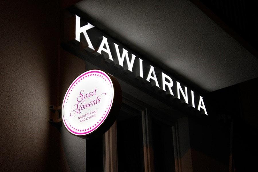 Białe litery podświetlane jako oznakowanie kawiarni