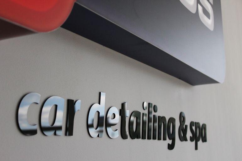 Logo podświetlane w recepcji salonu